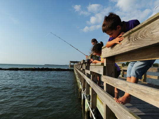 Brayden Dycus, right, keeps a watchful eye on the bobber at the end of his friend Lynnze Ruland's fishing line while fishing off the Cape Charles Pier.
