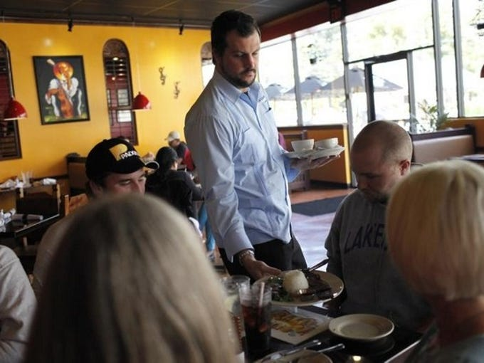 Oscar Pita, center, serves customers at Havana Rumba Express & Tapas Bar located on Bardstown Rd. in the Highlands. Oct. 18, 2013