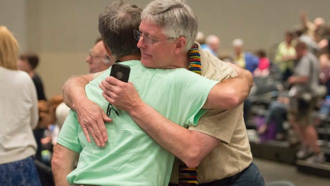 """Gary Lyon, of Leechburg, PA, left, and Bill Samford, of Hawley, PA., celebrate after a vote allowing Presbyterian pastors discretion in marrying same-sex couples at the 221st General Assembly of the Presbyterian Church at Cobo Hall, in Detroit, Thursday, June 19, 2014. The top legislative body of the Presbyterian Church (U.S.A.) voted by large margins to recognize same-sex marriage as Christian in the church constitution, adding language that marriage can be the union of """"two people,"""" not just """"a man and a woman."""" (AP Photo/The Detroit News, David Guralnick)"""