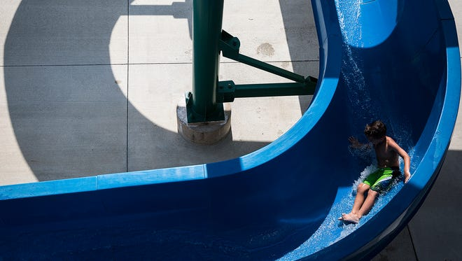 A young swimmer goes down the slide at Tuhey Pool in August 2016.