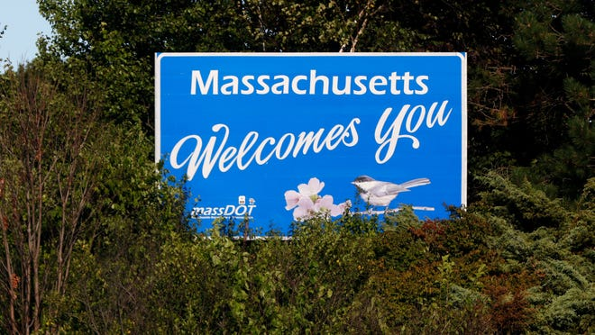"""FILE - A """"Massachusetts Welcomes You"""" sign at the Massachusetts-Rhode Island border on Interstate 95 south near Pawtucket, Rhode Island, Aug. 26, 2020."""