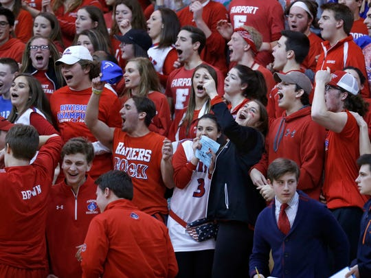 Fairport fans celebrate a basket by their team in the
