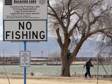 A woman and her dog walk on a chilly Tuesday along the path around Ascarate Lake. A sign near the lake warns against fishing. Some dead fish were seen floating in some areas of the lake, while live fish were seen swimming near the lake's edge.