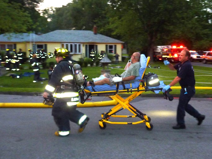 Indianapolis Fire Department and EMS take on of the fire victims to a waiting ambulance as others remain on the scene following a fire at 2718 Duane Drive Saturday . Four people were transported to area hospitals.