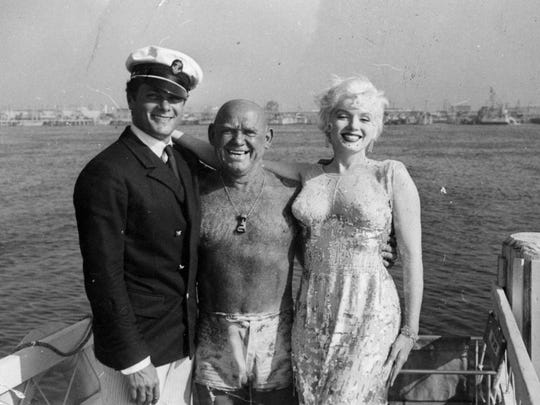 """Tony Curtis (left) and Marilyn Monroe, stars of the classic comedy, """"Some Like It Hot,"""" pose with the good-will ambassador of Catalina, Duke Fishman, outside of Avalon"""