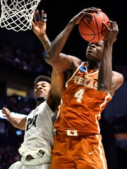 Texas forward Mohamed Bamba (4) grabs a rebound in front of Nevada forward Jordan Caroline (24) during the first half of their first round game in the 2018 NCAA Division I Men's Basketball Championship at Bridgestone Arena Friday, March 16, 2018 in Nashville, Tenn.