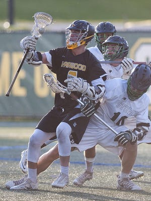 Harwood's Connor Woolley shields the ball from a trio of Stowe defenders during the second half of Friday night's Division II boys lacrosse championship game at Virtue Field.