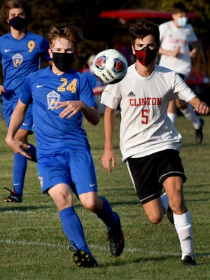 Eyeing the soccer ball Grantham Nelson of Ida and Nate Chavez of Clinton Monday evening.