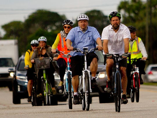 Steve Clark from the League of American Cyclists leads a group of Bonita Springs residents, planners and bicycle advocates inluding, Bonita Springs councilman Mike Gibson, left, on a tour of Bonita Springs. He is in Southwest Florida this week to talk to communities that are interested in applying to be bike-friendly communities, which helps tourism. Behind the group is a motorist that appears to be holding a mobile device.
