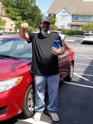 Taunton resident Wilfredo Aleman, who works at the Brockton VA Medical Center, holds up keys to his 2009 Toyota Corolla he recently received from Good News Garage.