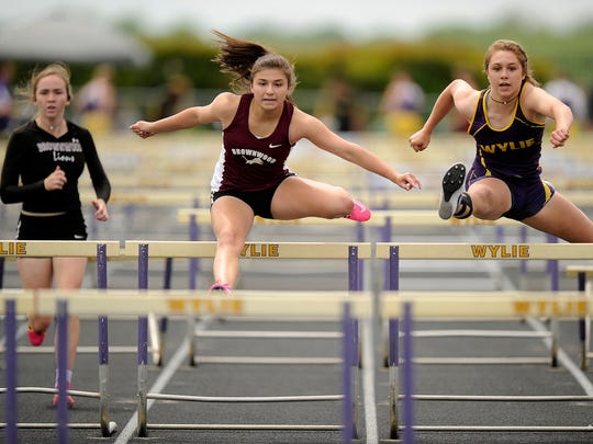 Brownwood's Trinity Buitron (center) clears a hurdle ahead of Wylie's Ambria Brekke (right) in the girls 100m hurdles during the District 5-4A track meet on Thursday, April 13, 2017, at Wylie's Bulldog Stadium. Buitron won the race, Brekke finished second.