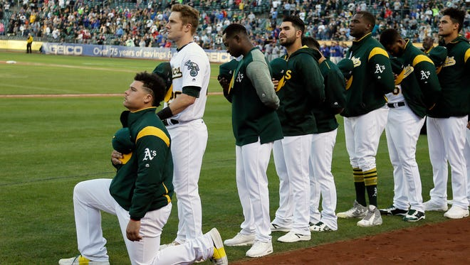 Oakland Athletics catcher Bruce Maxwell kneels during the National Anthem before the start of Saturday's game against the Texas Rangers at Oakland Coliseum.