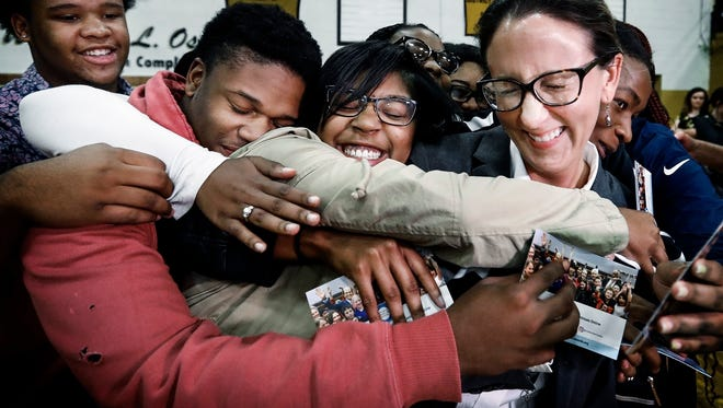 Millington Central High School English teacher Katherine Watkins (far right) receives congratulatory hugs from her 11th grade students after receiving a $25,000 Milken Educator Award during a surprise ceremony Thursday afternoon. The awards was created by the Milken Family Foundation in 1987 to recognizes teaching excellence.
