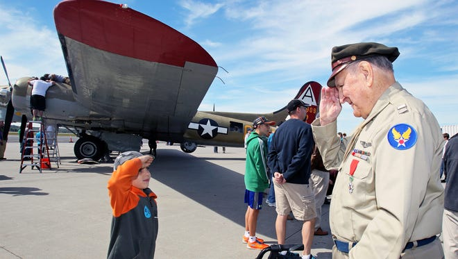 Gabriel Decoff, left, 9, of Spencer, salutes World War II Air Force veteran Bill Purple, right, in front of a B-17 bomber during the Wings of Freedom event at Worcester Regional Airport in Worcester.