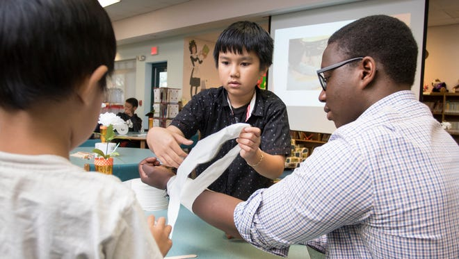 UWF junior Basil Kuloba, right, has brothers Duy Anh, 4, left, and Tien Nguyan, 10, make a splint on his arm out of popsicle sticks and toilet paper during the Inertia Education Program at Ensley Elementary School in Pensacola on Friday, April 27, 2018.