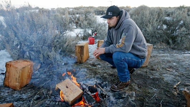 A member of the group occupying the Malheur National Wildlife Refuge headquarters warms himself by a fire Wednesday, Jan. 6, 2016, near Burns, Ore.