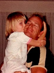 Brock Henderson, Kassi's father, embraces her in a