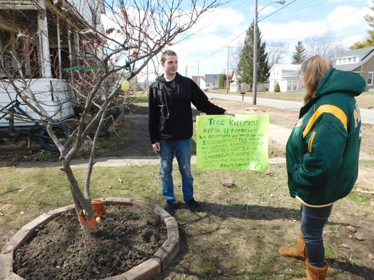 """Rhonda Van Fleet, right, was upset by the removal of trees along her Green Springs street so she posted a sign claiming removal of the 50 plus trees was """"arborcide."""" Her son Robert holds the sign next to one tree the family saved by moving it into their yard."""