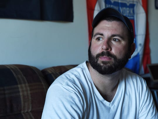 Frank Risole, 25 sits in his room at his parent's house,