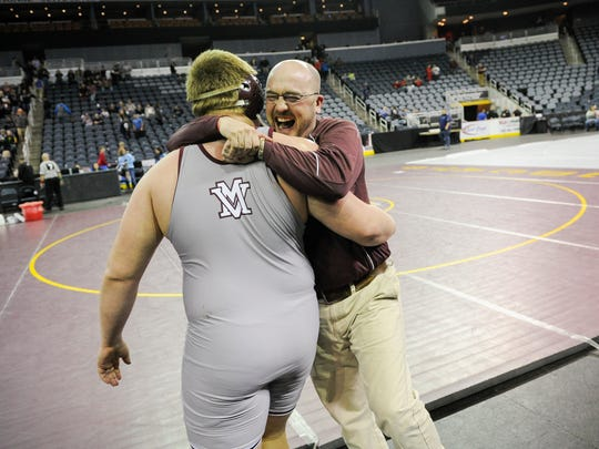 Mount Vernon's Wade Ripple celebrates with coach Tim Alcorn after his victory over Brownsburg's Rickie Clark in the 285-pound championship match during the Reitz wrestling semistate at the Ford Center, Saturday, Feb. 11, 2017.
