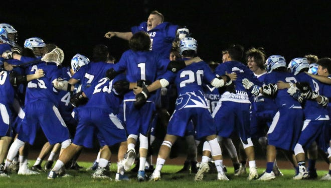 The Salem Rocks varsity boys lacrosse team celebrates after winning 10-9 in overtime Wednesday night against Plymouth.