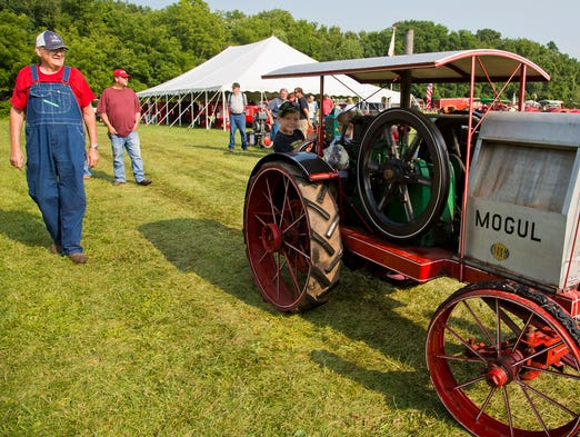 William Hedrick watches his grand children A.J. and Jessi Hedrick take his scale model of a 1911 Mogul tractor for a spin at the 34th annual Steam and Gas Power show look at some of the tractors Saturday, August 2, 2014, at the Tippecanoe County Amphitheater near West Lafayette.