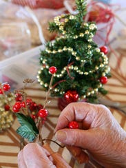 Careful hands extract tiny ornaments to decorate a