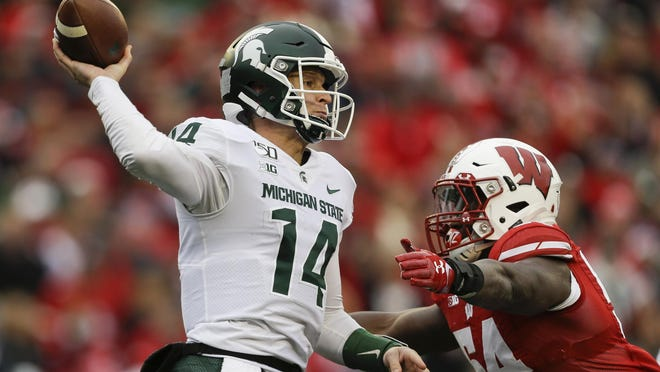 Michigan State quarterback Brian Lewerke (14) passes against Wisconsin linebacker Chris Orr (54) during the first half of an NCAA college football game Saturday, Oct. 12, 2019, in Madison, Wis.