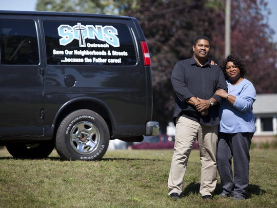 SONS Outreach executive director Tyrone Burrell stands with his wife Laura Burrell Wednesday, September 16, 2015 at 3001 Electric Ave. in Port Huron. An anonymous buyer donated the 9.5-acres of vacant land to SONS Outreach after closing on the sale Tuesday.