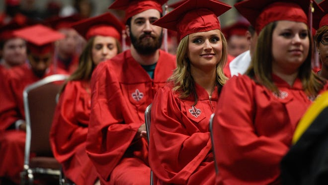 In this file photo University of Louisiana at Lafayette students smile during graduation. The Lafayette school is among few not receiving dramatic cuts from the state at this point.