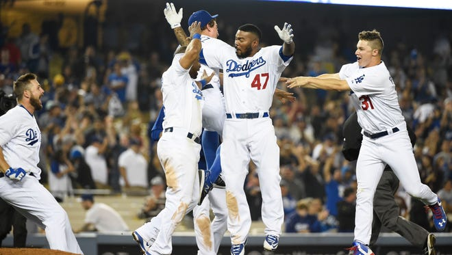 June 10, 2015; Los Angeles; Los Angeles Dodgers second baseman Howie Kendrick celebrates with teammates after his walk-off hit in the ninth inning against the Arizona Diamondbacks at Dodger Stadium.