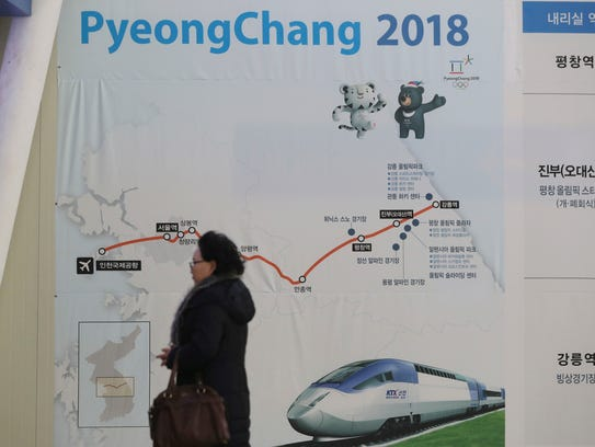 A visitor walks by the banner of train route from Incheon