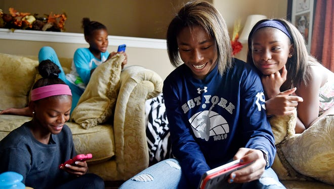 From left, sisters Trinity Thomas, 16; Tristen, 10; Tesia, 14; and Taelyn, 11, compare their Dubsmash lip sync videos while relaxing in their West Manchester Township living room Friday, Sept. 1, 2017. Trinity Thomas, 16, and Tesia Thomas, 14, are different athletes in their own right, but each excels in her chosen discipline. Trinity Thomas is a gymnast on the U.S. senior national team who will attend Team USA's selection camp this month for a shot at a place on the squad for the world championships. Tesia Thomas is a standout three-season athlete for West York, where she plays volleyball, swims and is on the track and field team.
