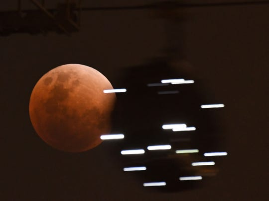 "A cable car gondola moves past as the moon is seen during a lunar eclipse, referred to as the ""super blue blood moon,"" in Singapore on Jan. 31."
