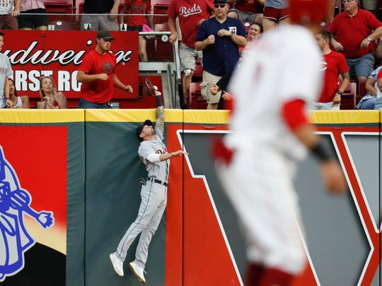Nicholas Castellanos, left, misses a grand slam by the Reds' Joey Votto, June 19 in Cincinnati.