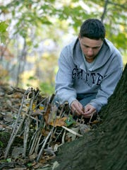 Darron Kriegel of Irondequoit creates a miniature shelter with sticks and leaves during a survival skills beginner class at Tryon Park.
