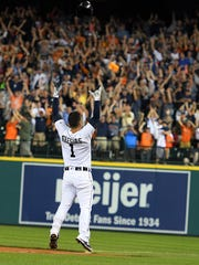 Tigers shortstop Jose Iglesias throws his batting helmet as he celebrates with fans after hitting a walkoff RBI-single in the ninth inning of the Tigers' 3-2 win over the Astros Saturday at Comerica Park.