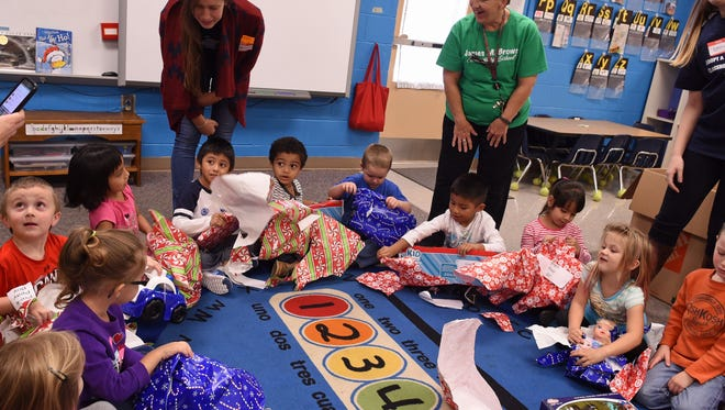 James M. Brown Elementary School students in Walhalla open Christmas present delivered by Clemson University students as part of a new mentoring program.