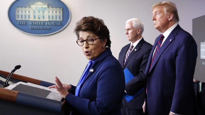 FILE - In this Thursday, April 2, 2020 file photo, Jovita Carranza, administrator of the Small Business Administration, speaks about the coronavirus in the James Brady Press Briefing Room of the White House n Washington, as Vice President Mike Pence, President Donald Trump listen. Millions of small businesses are expected to apply for a desperately needed rescue loan Friday, a stern test for a banking industry that has had less than a week to prepare for the deluge. Small businesses will be seeking loans from the $349 billion Paycheck Protection Program, which was put in place to help them retain workers and pay bills during the coronavirus pandemic.