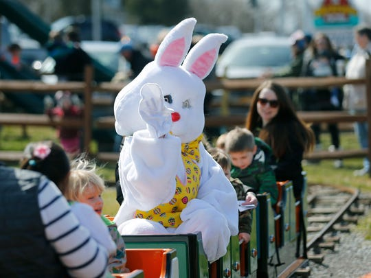 In a bunny costume, Jordan McNaughton of Penfield rides the train while waving at kids during the Bunny Hunt at Wickham Farms.