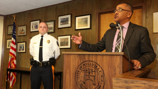 Mayor Michael Santiago talks about newly promoted police Lt. Carl Heger, left, at a Millville City Commission meeting in February.