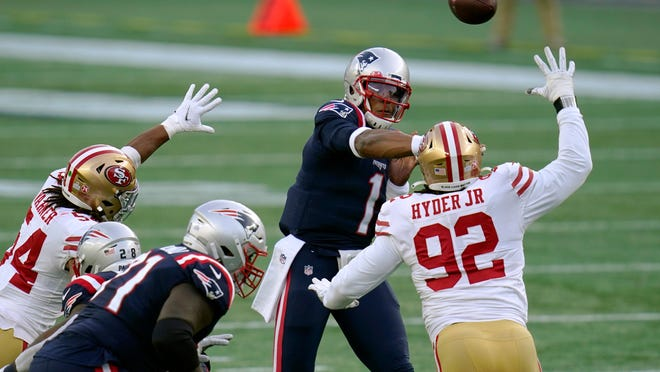 New England Patriots quarterback Cam Newton, rear, passes under pressure from San Francisco 49ers defenders Fred Warner (54) and Kerry Hyder Jr. (92) in the first half of an NFL football game, Sunday, Oct. 25, 2020, in Foxborough, Mass.