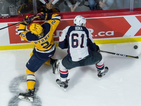 Windsor forward Luke Boka (61) battles against Erie's