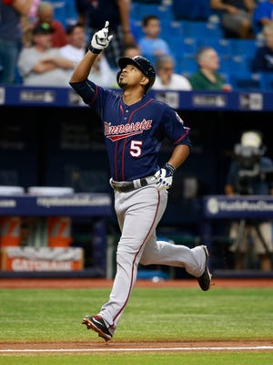 Twins shortstop Eduardo Escobar points up as he celebrates while running home as he hits a solo home run during the sixth inning.