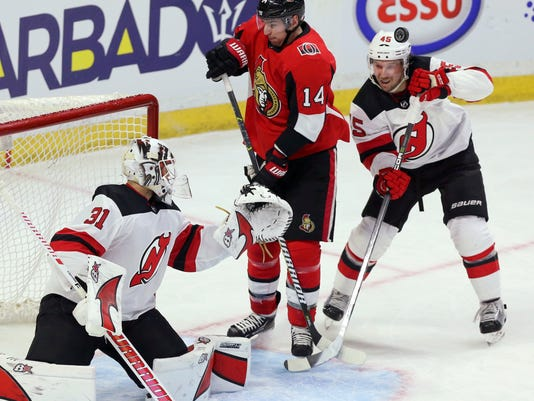 Ottawa Senators' Alexandre Burrows (14) and New Jersey Devils' Sami Vatanen (45) react as the puck comes off the goal post behind goaltender Keith Kinkaid during the third period of an NHL hockey game Tuesday, Feb. 6, 2018, in Ottawa, Ontario. (Fred Chartrand/The Canadian Press via AP)
