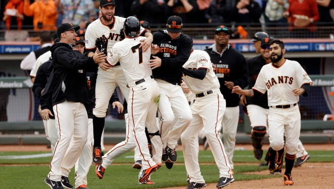 The Giants celebrate after scoring in the 10th inning to beat the Cardinals 5-4 on Tuesday.