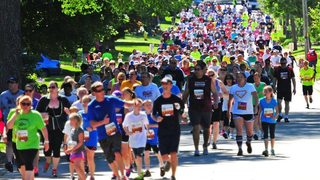 Runners and walkers take the turn on S. Clay Street at Hastings Street during the 2014 Bellin Run, Saturday, June 14, 2014.
