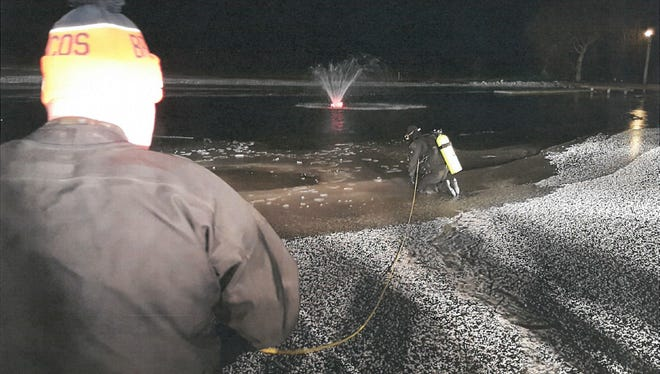 A diver gets set to enter an icy pond where a Johnson County man died on Tuesday.