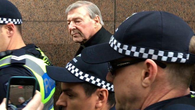Cardinal George Pell, rear center, Australia's highest-ranking Catholic and Pope Francis' top financial adviser, leaves Melbourne Magistrates' Court Wednesday, July 26, 2017.