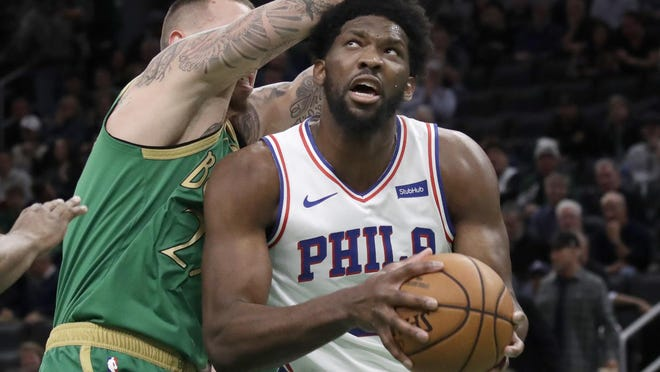 76ers center Joel Embiid looks to shoot against the Celtics' Daniel Theis in a game last December. The smaller Boston team has struggled against bigger players like Embiid all season.